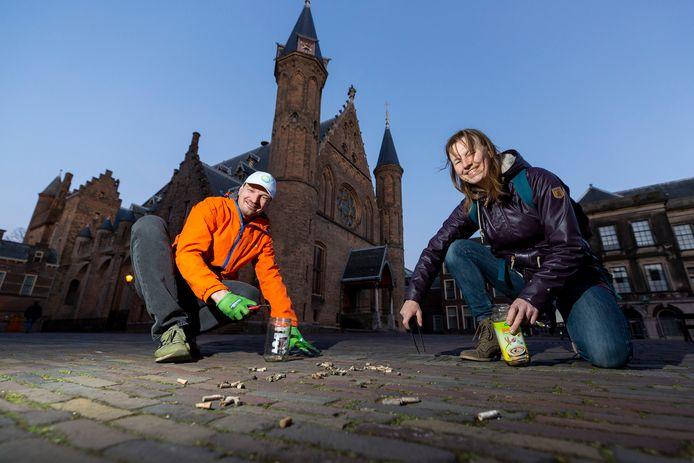Suze Stiphout en Cliff Nijssen zijn op het Binnenhof met hun barbecuetang peuken aan het opruimen. 'Eén peuk vervuilt door plastic en chemicaliën 8 liter water.'
