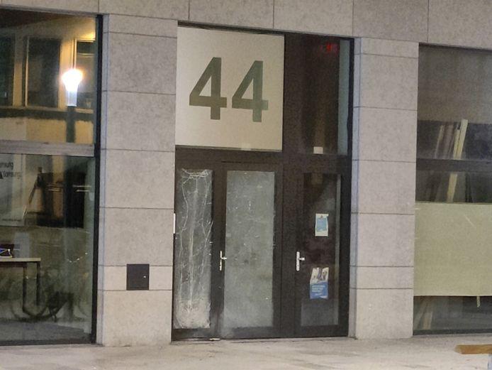 De voordeur van het gebouw was zwaar beschadigd door de impact.