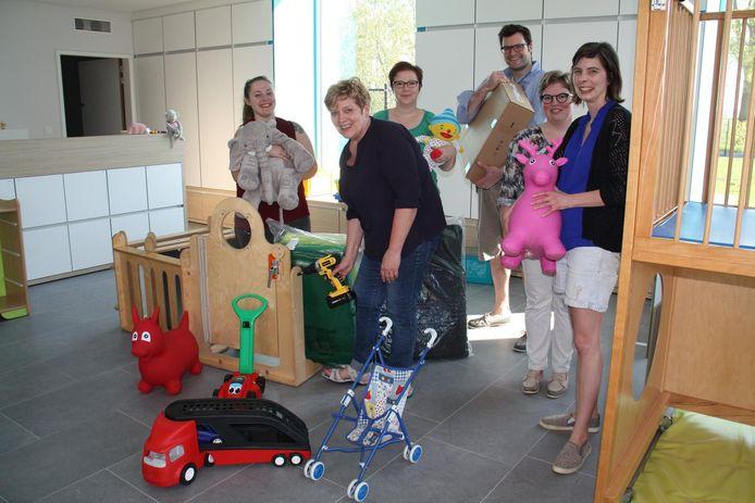 Ouders helpen het speelgoed en de bedjes verhuizen.