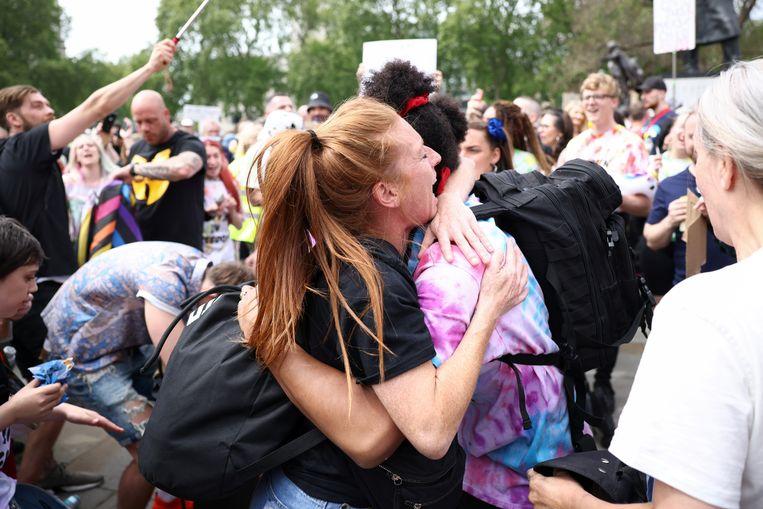 Twee mensen in een innige omhelzing, op een Londens protest tegen de maatregelen.  Beeld REUTERS