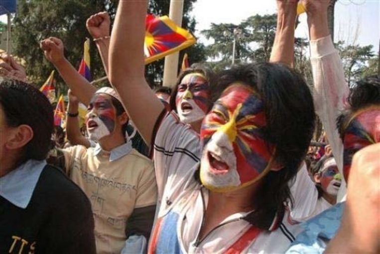 Tibetaanse demonstranten hebben de Tibetaanse vlag op hun gelaat geschilderd.