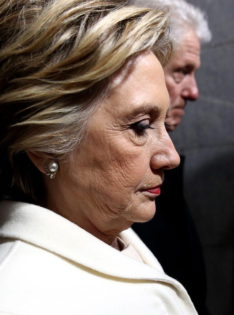 Een gespannen Hillary Clinton bijgestaan door haar man, oud-president Bill Clinton, vlak voor de inauguratie van Donald Trump in januari.  Beeld EPA