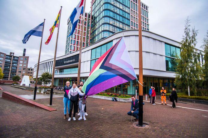 Wethouder Eugene van Mierlo (gehurkt) hijst de regenboogvlag voor het stadhuis in Almelo.