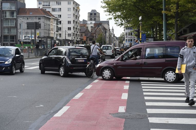 Een fietser slalomt tussen de auto's omdat het fietspad geblokkeerd is.