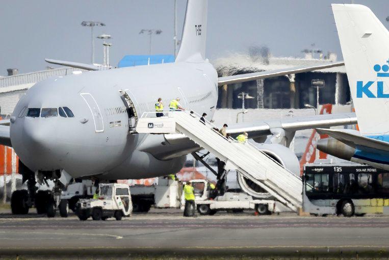 Evacués uit Afghanistan stappen uit bij een afgeschermd vrachtplatform op Schiphol.  Beeld ANP