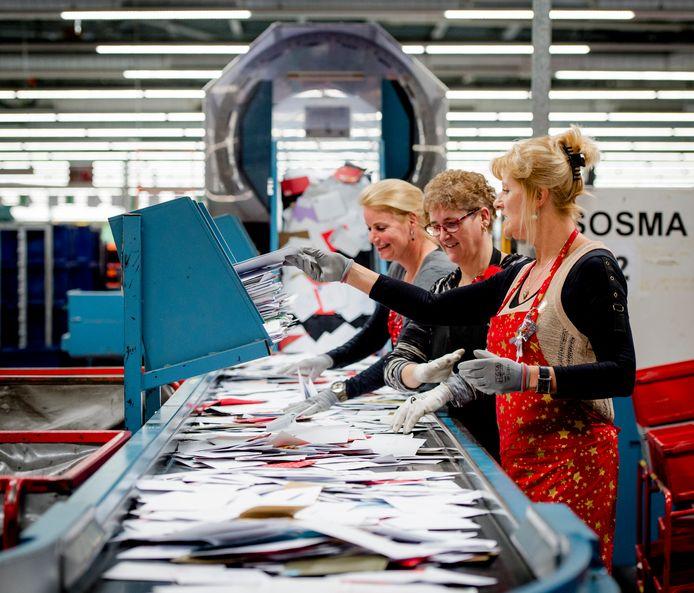 Kerstdrukte in een brievensorteercentrum van PostNL. Voor de pakketsorteerders is het werk fysiek veel zwaarder dan voor deze werknemers.