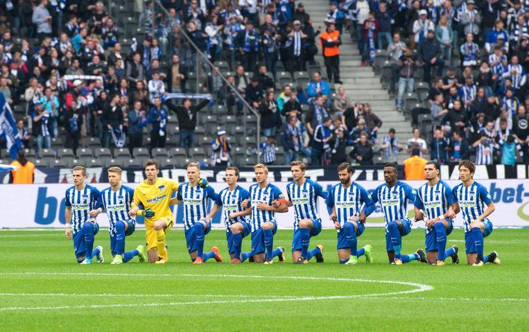 Als steunbetuiging aan Colin Kaepernick knielen de voetballers van Hertha BSC voor de wedstrijd tegen Schalke 04. Beeld AFP