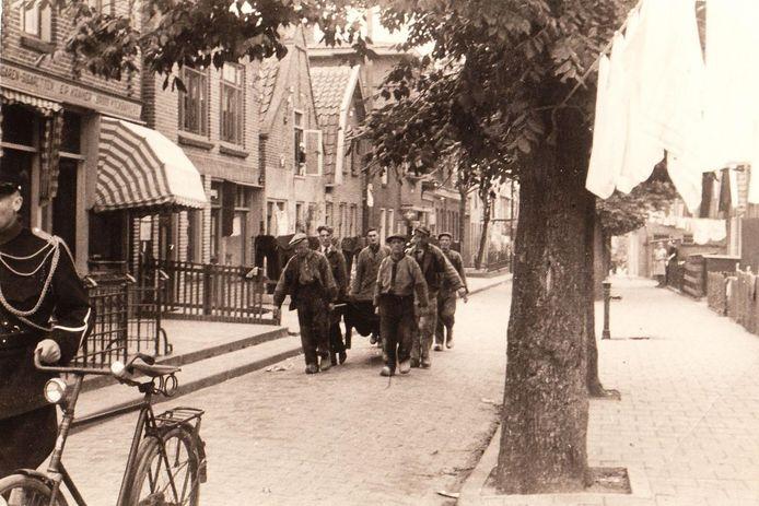 Gemeentearbeiders dragen op Urk de kist met het stoffelijk overschot van een geallieerde vlieger naar de haven. Het IJsselmeer was een belangrijke vliegroute voor geallieerde vliegtuigen die in Duitsland bombardementen uitvoeren. Veel omgekomen piloten spoelden op Urk aan. De man met de fiets aan de hand is mogelijk opperwachtmeester van de politie Harmen Visser. Hij was tot 1943 hoofd van de politie van Urk en actief in het verzet. Op 16 april 1945, één dag voor de bevrijding van de polder, sneuvelde hij bij Kuinre.