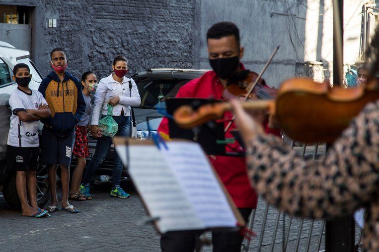 Studenten spelen muziek op straat in São Paulo, Brazilië. De groep studenten wil vermaak bieden tijdens de pandemie.  Beeld AP