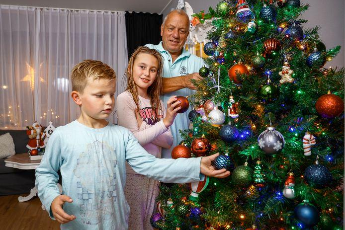 Gerrit Agterbosch versiert met zijn kleinkinderen Diego (6 jaar) en Rosemary (9 jaar) de kerstboom.