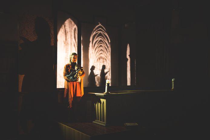 Ann De Prest op scène, met achter haar bewegende schimmen