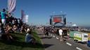Zittend op de dijk volgen mensen de optredens.
