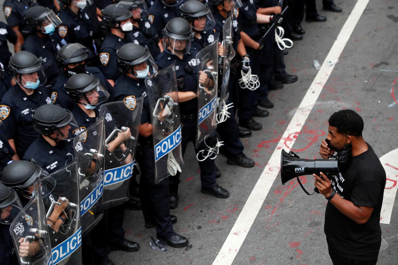 Een betoger tegenover politieagenten op 1 juli vorig jaar in New York.  Beeld REUTERS