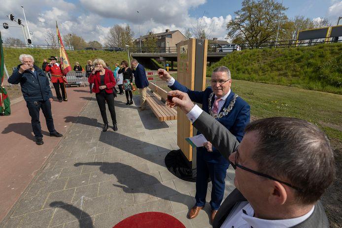 Burgemeester Marcel Delhez en wethouder Hans van de Looij (vooraan) proosten met onder meer familieleden van 100-jarigen op het 100-jarig bestaan van de gemeente. Op de zuil bij het nieuwe 100-jarigenbankje staan nu al namen van vier Veldhovense eeuwelingen.
