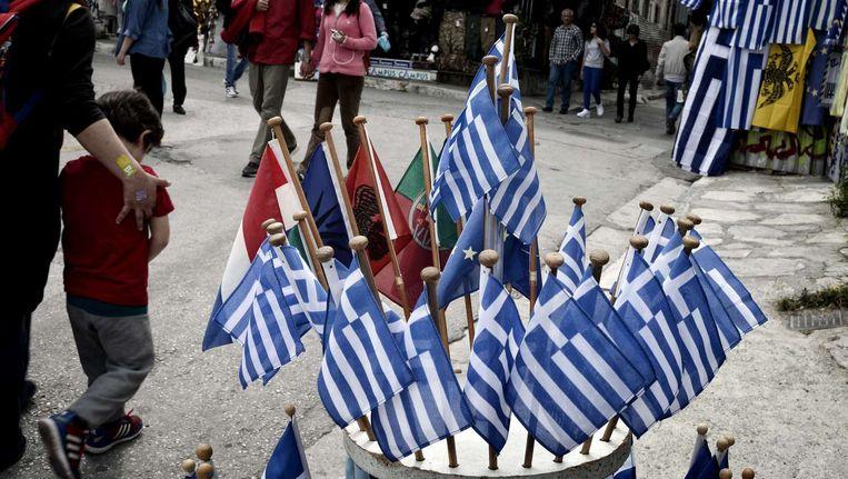 Griekse vlaggetjes bij een winkel in Athene. Beeld afp