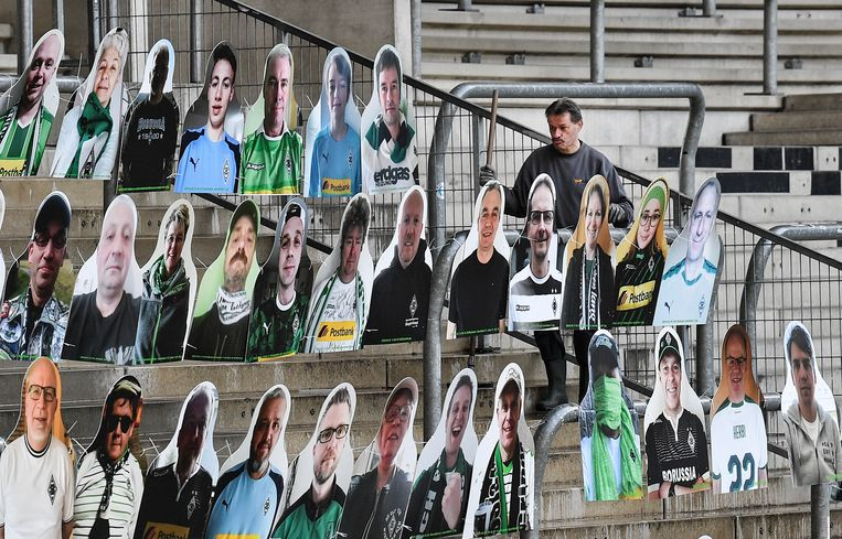 De klusjesman van Borussia Mönchengladbach plaatst de supporters van bordkarton in de tribune. Beeld AP