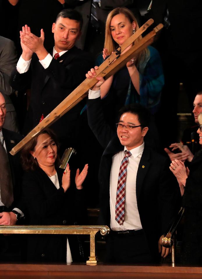 Ji Seong-ho steekt zijn krukken op naar het juichende publiek tijdens de State of the Union