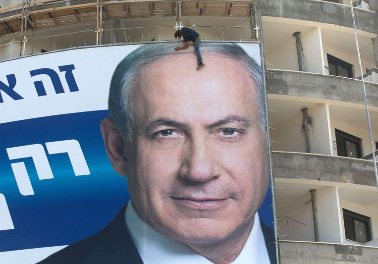 ► Arbeiders hangen een enorme affiche op van Israëlisch premier Netanyahu in Tel Aviv, in de aanloop naar de verkiezingen in 2015. Beeld AFP