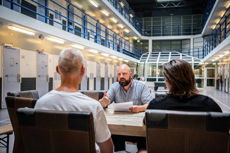 Toon Molleman, gevangenisdirecteur in de penitentiaire inrichting in Arnhem, vertelt twee leden van de gedetineerdencommissie dat een deel van de strenge coronamaatregelen komt te vervallen.