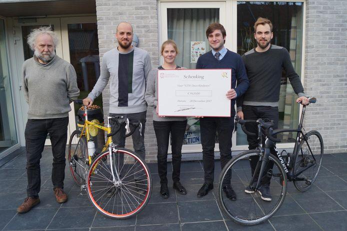 Mathieu Vancanneyt van Chateau Residenties overhandigt de cheque aan Kim Den Baes. Links Marc Vermeulen, met de fiets aan de hand Jasper Dejonckheere en Toon Wybo.