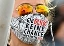 Een demonstrant in Berlijn wijdt haar mondkapje aan Bill Gates.