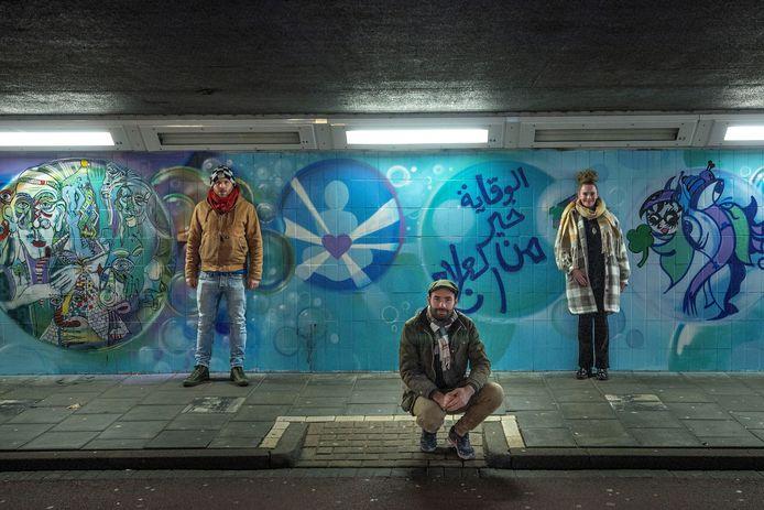 Eindhoven - Burst your bubble! Dat is de boodschap van het kunstwerk dat een groep 'outsider artists', aanbracht op de muren van de Kruisstraattunnel. Op de foto deelnemers Job (l) en Sonja (r) met graffitikunstenaar Niels Bakkerus.