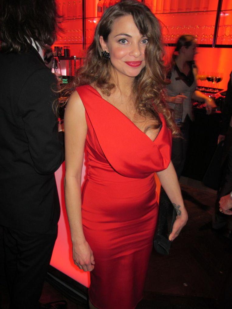 Rood en rondborstig is Georgina Verbaan in een jurk van Jos van Raak. <br /><br /> Beeld