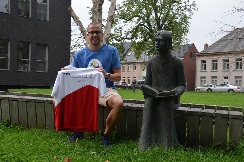 Topzwemmer Jasper Aerents bracht een gesigneerd olympisch truitje mee als cadeau voor het gemeentepersoneel. Hij poseert naast het standbeeld van Diederik van Assenede.