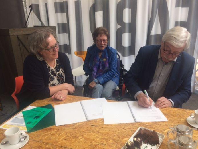 Wethouder Frans van den Berg (rechts) tekent het convenant. Links kijkt voorzitter Jeanny Rutten van de stichting Drempels Weg Uden toe.