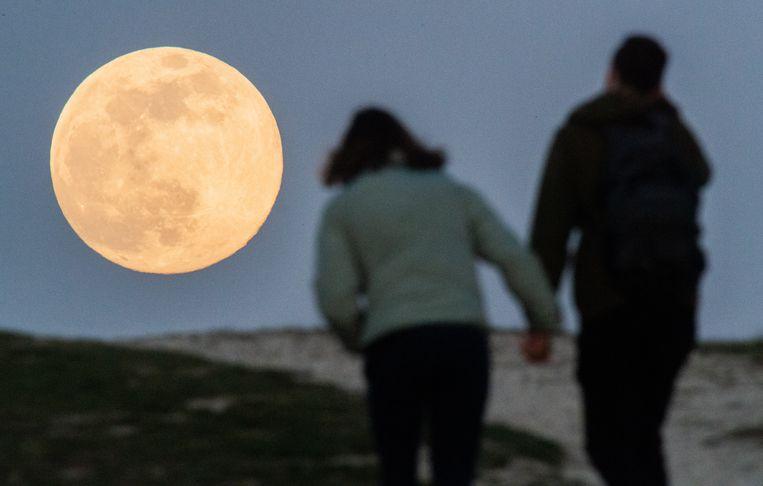 Een koppel in Hanover (Duitsland) bewondert de maan tijdens een wandeling. Beeld Julian Stratenschulte/dpa