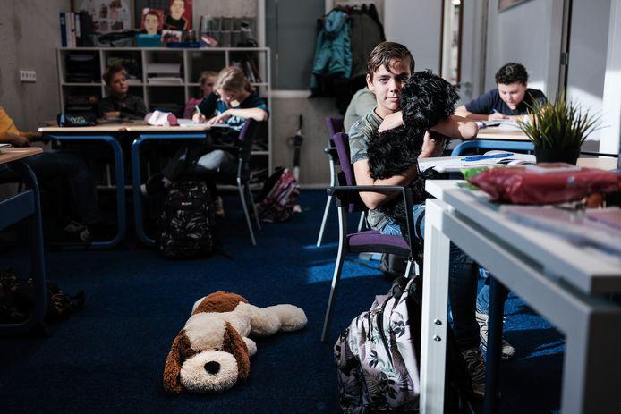 Schoolhond Teddie met Guus in de klas bij wiskunde.