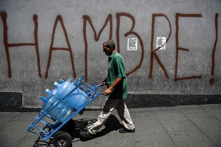 Een man duwt bidons voort langs een muur met daarop 'Hambre!' of 'Honger!' in graffiti. Beeld AFP