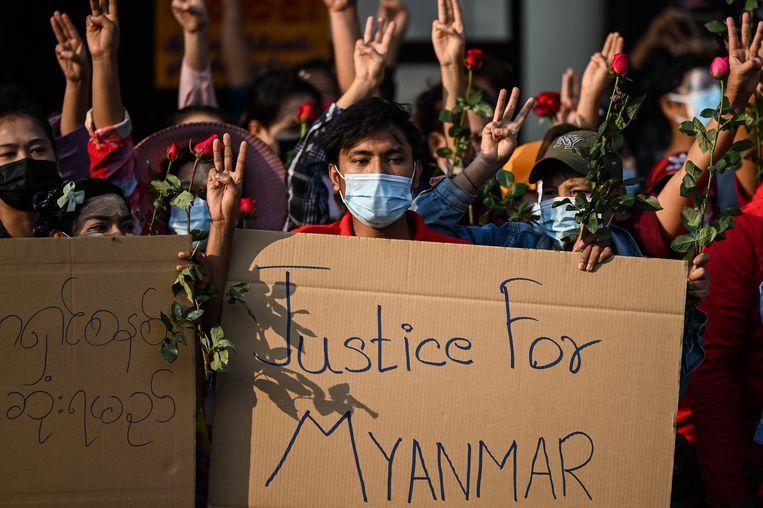 Demonstranten zondag in Yangon, Myanmar, met plakkaten, bloemen en drie vingers in de lucht als protestgebaar tegen de militaire staatsgreep. Beeld AFP