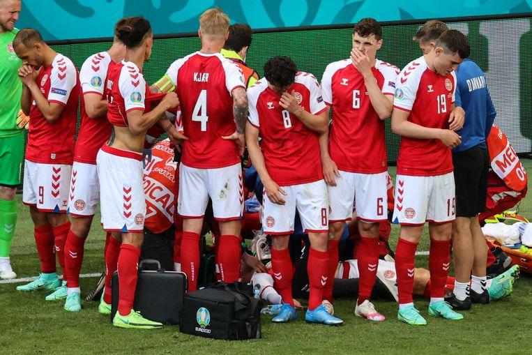 Spelers van Denemarken verzamelen zich op het veld om Eriksen heen Beeld AFP