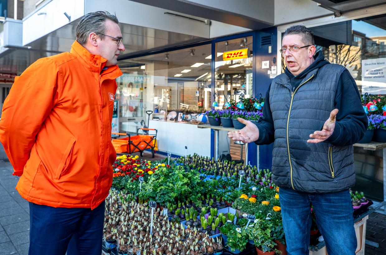 Lijsttrekker Richard de Mos van Code Oranje in gesprek met een bloemenverkoper in winkelcentrum Zevenkamp in Rotterdam.  Beeld Raymond Rutting / de Volkskrant