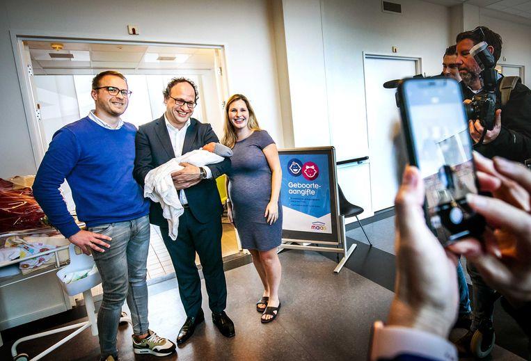 Minister Wouter Koolmees van sociale zaken met twee jonge ouders  en hun pasgeboren baby. Koolmees was daar omdat de vader een van de eerste mannen was die vijf dagen betaald verlof kreeg bij de geboorte van zijn kind. De wet ging in 2019 in. Beeld ANP