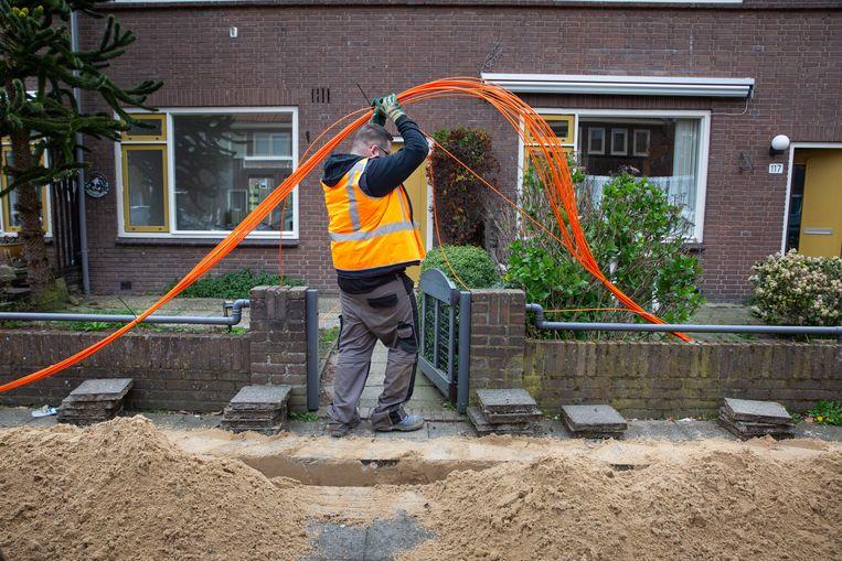 KPN legt glasvezel in Zwolle-Noord. In Dieze, een arbeiderswijk uit de jaren dertig, worden glasvezelkabels onder het trottoir gelegd.  Beeld Herman Engbers