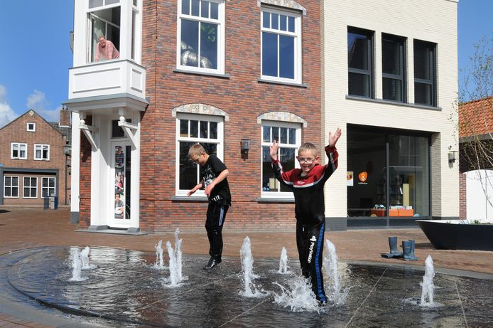 De nieuwe fontein op het Kerkplein in Bruinisse is vandaag in werking gesteld en daar maakten broers Tommy (l) en Martin van der Wielen gelijk een feestje van.
