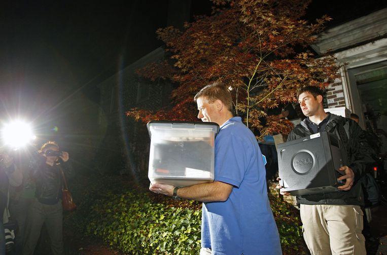 FBI-agenten dragen dozen en een computer uit het huis van Broadwell. Beeld ap