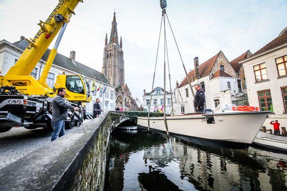 De eerste elektrische toeristenboot wordt met een hijskraan te water gelaten.