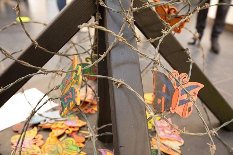 De prikkeldraad symboliseert het opsluiten en vermoorden van mensen die 'anders' zijn, in concentratiekampen.