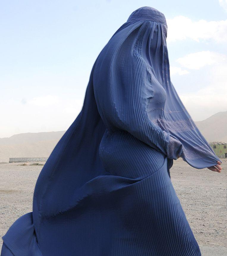 Een in boerka geklede Afghaanse vrouw op een heuveltop die uitkijkt op Kaboel.  Beeld AFP