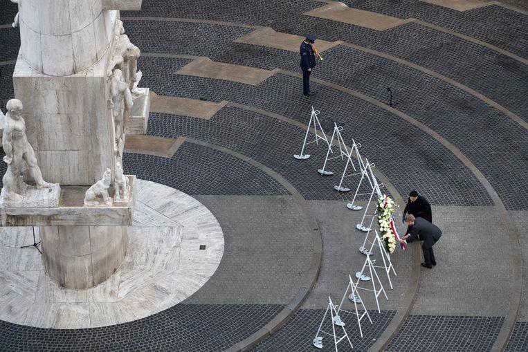 Koning Willem-Alexander en koningin Máxima leggen een krans bij het Monument op de Dam. Beeld AP