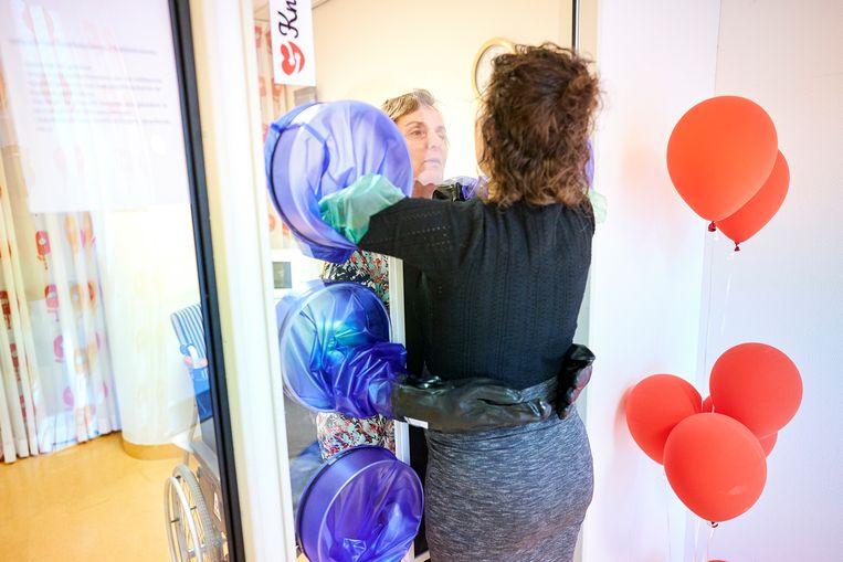 Kim Warmerdam omhelst met haar moeder via de door haar bedacht 'knuffelmuur'. Beeld Phil Nijhuis