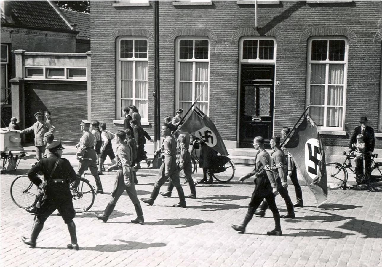 Leden van de NSDAP, veelal Duitsers, marcheerden in de jaren dertig door de straten van Eindhoven, met de hakenkruisvlaggen. FOTO RHCe