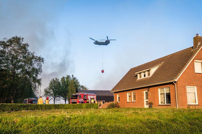 De brandweer probeert het vuur in de Deurnsche Peel weg te houden van een boerderij in Liessel.
