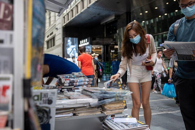 Een vrouw koopt vrijdagochtend een exemplaar van de pro-democratische krant Apple Daily bij een kiosk in Hongkong. Beeld EPA