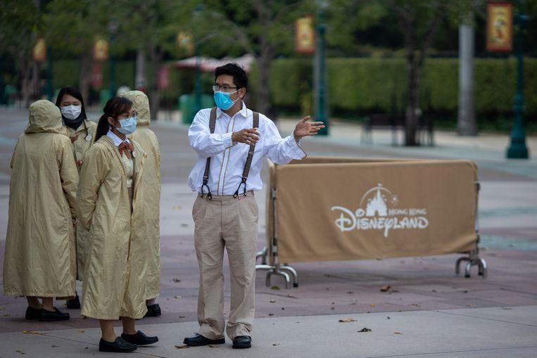 Personeel bij de ingang van Disneyland Hongkong, dat vanwege het coronavirus voorlopig gesloten blijft.  Beeld EPA