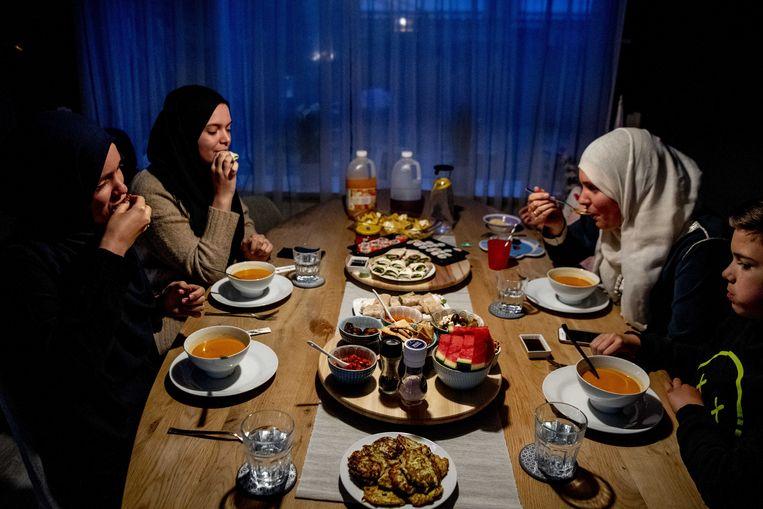 Een gezin aan tafel tijdens de iftar, de maaltijd na zonsondergang, tijdens de islamitische vastenmaand Ramadan. Beeld ANP