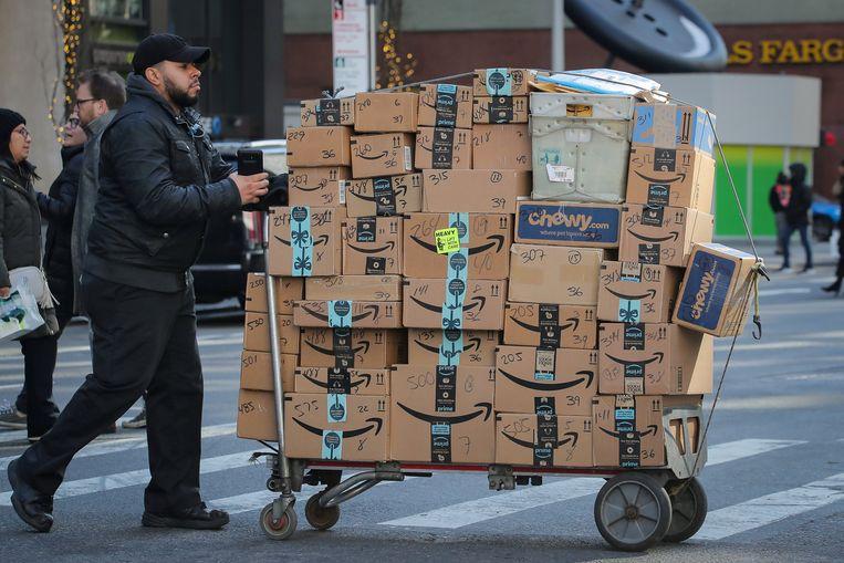 Een bezorger in New York op weg met een karretje vol Amazon-dozen. Beeld REUTERS